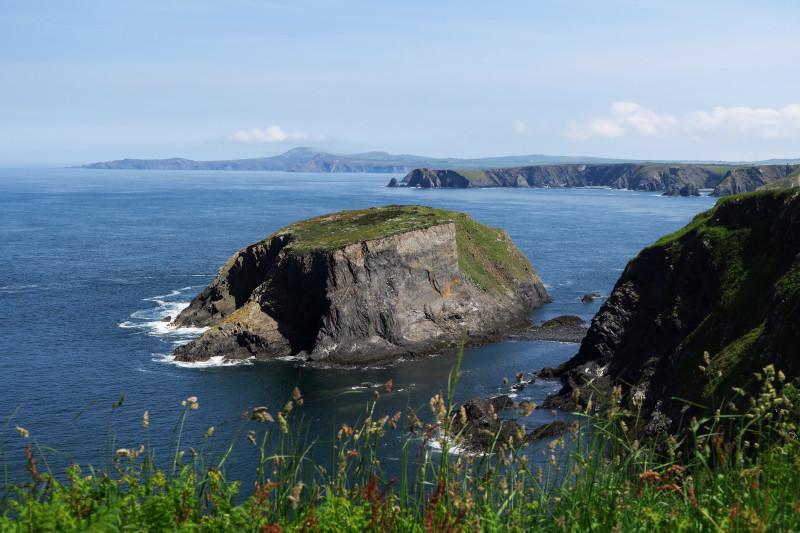 An der Küste von Pembrokeshire liegt ein riesiger zerklüfteter Felsen im blauen Wasser