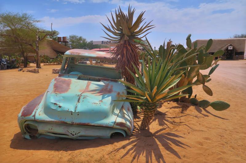 Ein verrostetes blaues Autowrack liegt im Wüstensand
