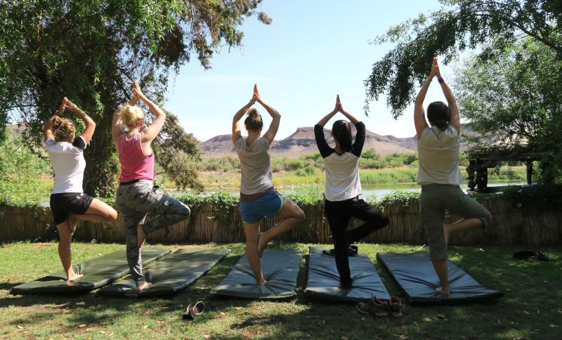 Fünf Frauen beim Yoga mit Blick auf den Orange River in Südafrika